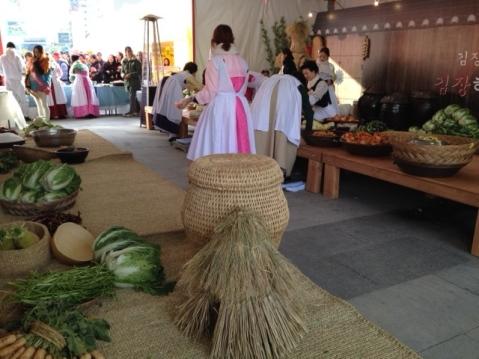 Women wearing hanboks making kimchi